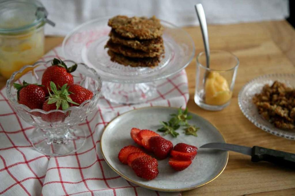 Auf diesem Bild sieht man einen Tisch von oben. Auf dem Tisch steht ein Teller mit geschnittenen Erdbeeren, eine Schüssel mit angeschnittenen Erdbeeren und einen Tortenständer mit Knuspertörtchen.
