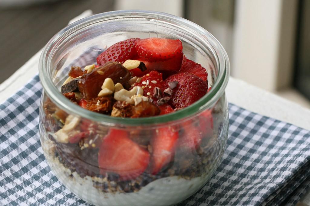Auf dem Bild sieht man ein Glas gefüllt mit Joghurt, welcher mit Erdbeeren und Müsli getoppt wurde.